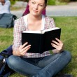 Bright female student reading a book sitting on the grass — Stock Photo