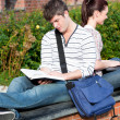 Couple of students using a laptop and reading a book sitting — Stock Photo
