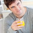 Attractive young man drinking orange juice in the kitchen — Stock Photo #10835166