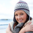 Pretty woman with scarf and colorful hat standing on the beach — Stock fotografie