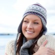 Pretty woman with scarf and colorful hat standing on the beach — Stock Photo