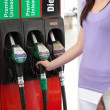 Close-up of a young woman refueling her car - Stock Photo