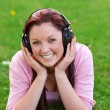 Delighted young woman listening to music with headphones lying on the grass — Stock Photo