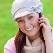 Pretty young woman wearing cap and scarf talking on phone on the grass — Stock Photo