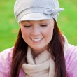 Pretty young woman wearing cap and scarf sending a message with her cellphone on the grass — Stock Photo