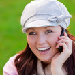Laughing young woman wearing cap and scarf talking on phone on the grass — Stock Photo