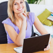Bright woman using laptop sitting in the living-room smiling at — Stock Photo