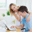 Bright caucasian couple having fun in front of a laptop — Stock Photo #10835405