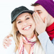 Young man with cap whispering something to his female friend — Stock Photo #10835439