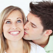 Stock Photo: Careful mkissing his smiling girlfriend against white backg