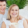 Laughing couple eating pop-corn lying on the sofa in the living- — Stock Photo