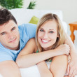 Smiling beatiful couple sitting on a sofa — Stock Photo