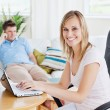 Beautiful couple. Woman using laptop — Stock Photo