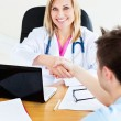 Stock Photo: Smiling doctor shaking hand of her patient