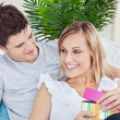 Beautiful couple lying on the sofa with a present — Stock Photo