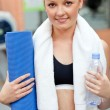 Sporty woman holding bottle of water and exercice mat looking at — Stock Photo