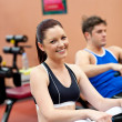 Beautiful woman using a rower with her boyfriend in a fitness ce - Stock Photo