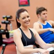 Beautiful woman using a rower with her boyfriend in a fitness ce — Stock Photo