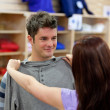 Handsome man with his girlfriend trying on clothes in a shopping — Stock Photo