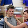 Stock Photo: Cute womchoosing clothes for her boyfriend in shop