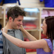 Cheerful couple choosing clothes standing in the men department — Stock Photo