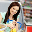 Cute woman putting bananas in her shopping-basket in a grocery s — Lizenzfreies Foto