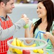 Handsome salesman giving apples to a happy customer in a grocery — Stock Photo