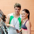 Pretty woman on a treadmill with her coach showing results — Stock Photo #10835700
