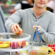 Close-up of a young man putting apples in his shopping basket — Stock Photo