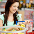 Portrait of an attractive woman buying bananas and apples — Stock Photo