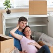 Adorable couple sitting on the floor in their new house during r - 