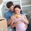 Cheerful couple celebrating pregnancy and removal with champagne — Stock Photo #10835758