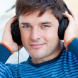 Royalty-Free Stock Photo: Peaceful man listening music using headphones smiling at the cam