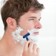 Portrait of a serious man shaving looking away standing in the b — Stock Photo