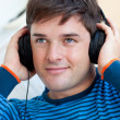 Portrait of a handsome man listening music with earphones — Stock Photo