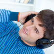 Stock Photo: Happy young man with headphones relaxing with music on the sofa