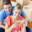 Cheerful couple celebrating their new house with champagne — Stock Photo #10835908