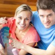 Bright couple choosing colour for their new house sitting in the — Stock Photo
