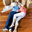 Happy couple lying on the floor in their new house doing thumbs- - Stock Photo