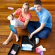 Young couple sitting on floor smiling - Photo