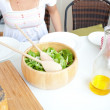 Close-up of a table with salad, oil and bread and of a yong woma - Stock Photo