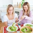 Two merry female friends eating salad in the kitchen — Stock Photo
