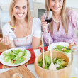 Two positive female friends eating salad in the kitchen — Stock Photo