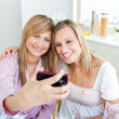 Two radiant female friends taking pictures during a birthday par — Stock Photo
