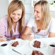 Stock Photo: Merry female friends eating a chocolate cake in the kitchen