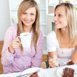 Joyful female friends eating a chocolate cake and drinking in th - Stock Photo