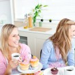 Royalty-Free Stock Photo: Two laughing female friends eating pastries and drinking coffee