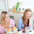 Two cheerful female friends eating pastries and drinking coffee — Stock Photo