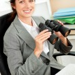 Smiling hispanic businesswoman holding binoculars sitting at her — Stock Photo