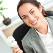 Bright hispanic businesswoman holding a light bulb sitting at he — Stock Photo